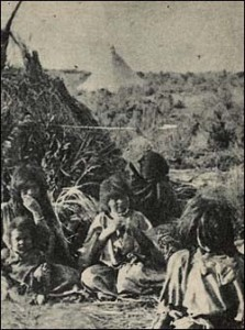Bannock women and children outside brush shelter.
