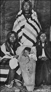 A group of women with child in cradle, in typical Shoshone lodge.